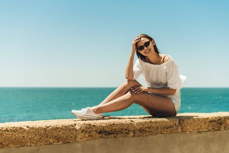 happy girl looks through black glasses sitting on the parapet of the beach. ocean background