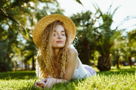curly blonde shrugs covering her eyes lies her stomach on the park grass Stockfoto