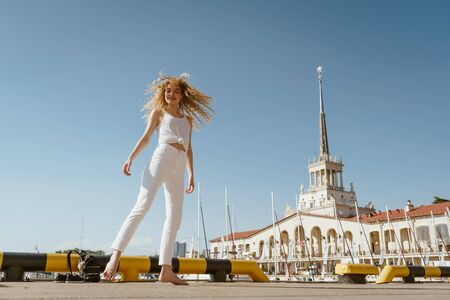 girl in white trousers and a blouse against the background of the seaport and ship masts