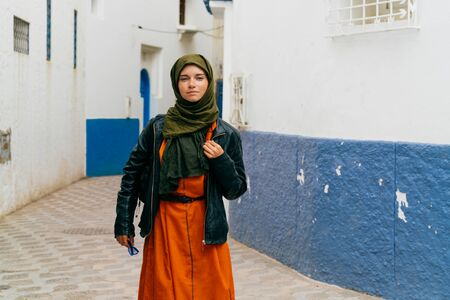 a girl in a leather jacket on top of clothes of residents of Morocco, in a scarf, with a backpack on a street in Morocco 版權商用圖片