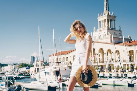 curly blonde walks lightly on a pier amid yachts, boats and a sea terminal
