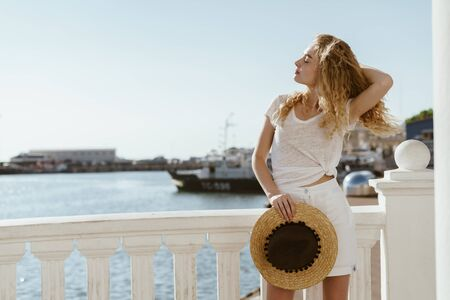 the sea breeze disheveled the curly hair of a beautiful blonde standing on the promenade, amid a floating ship Stock Photo