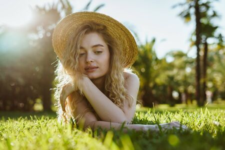 a cute girl, as if in a fairy tale, lies on her stomach and looks in front of herself on the grass. the suns rays illuminate the hair, hat, romantic