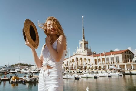 blonde with a magnificent joyful smile, straightens her hair disheveled by the wind and holds her hat against the background of the sea terminal
