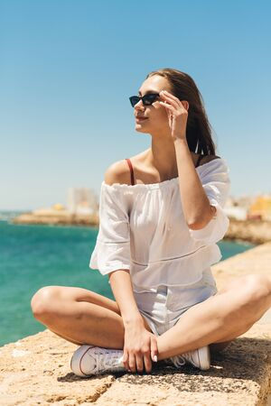 young girl in a light white blouse and dark glasses looks into the sea distance sitting in a lotus position on the shore 写真素材