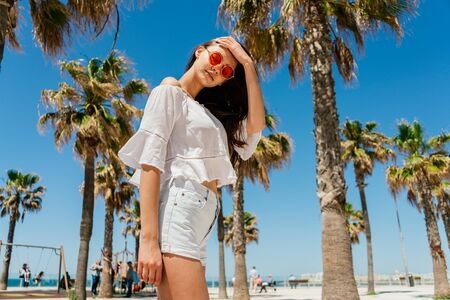 girl happily straightens her luxurious long hair on the beach on a background of palm trees 写真素材