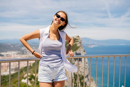the girl leaned her back and hands on the railing of the bridge and smilingly looks through her dark glasses. behind mountains and the ocean below