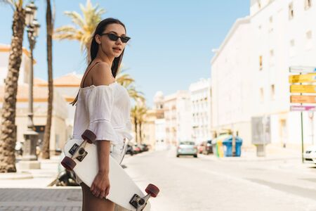 spa girl in a southern city in white clothes, among white houses. in her hand is a skate board 写真素材