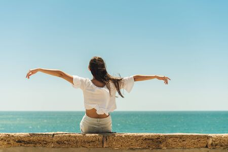 the girl turned her back on the spectator spread her hands to the sides and looks at the sea while sitting on the parapet