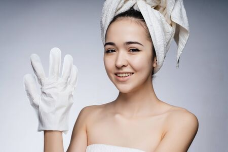 Asian at the beautician, wears gloves for hand care. towel on the head, shoulders bare Stock Photo