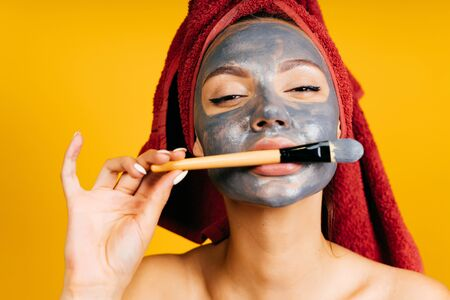 a girl with a black cosmetic mask on her face playfully holds her brush for applying a mask with her lips and hand. background yellow Фото со стока