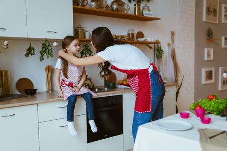 a girl sits on the kitchen table, while mom straightens her hair