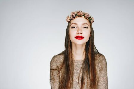 girl - bright autumn with red lips and a wreath of roses on her hair. gray background
