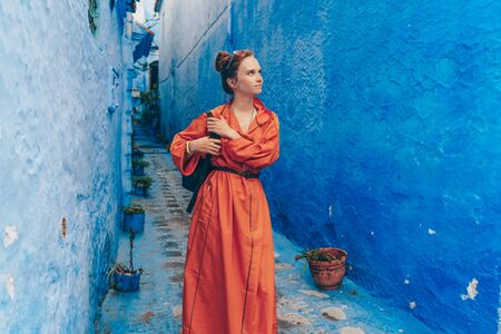 a tourist in a long bright orange dress with a backpack walks through the blue city of Morocco