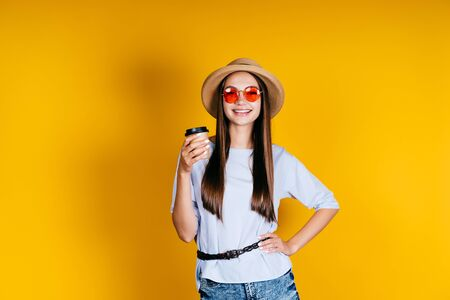 girl joyfully shows a cup of coffee in her hand and smiles broadly. background yellow Banco de Imagens