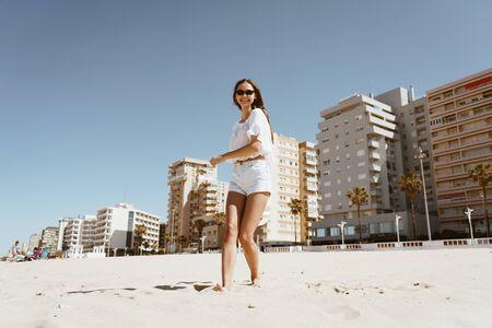 girl on the beach runs kicking sand