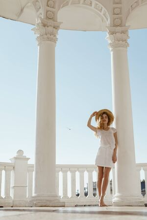 blonde in white clothes is standing in the gazebo with snow-white columns