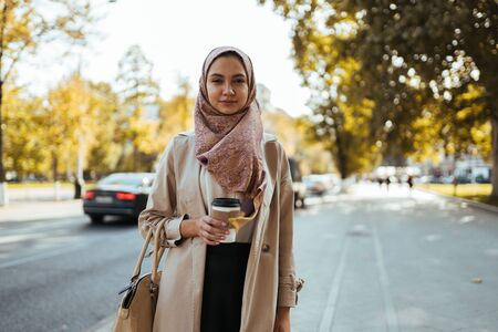 muslim woman in business clothes and a scarf with coffee in hand on a city street Banco de Imagens