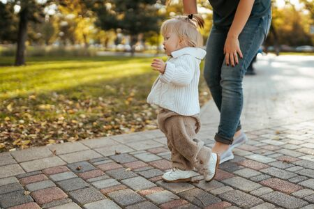 baby learns to walk, the first steps in the park by the handle with an adult