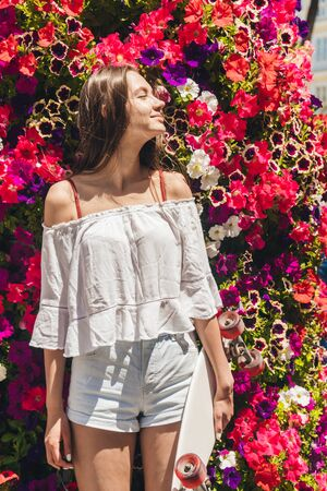 a brunette with a blouse, ala, a young peasant girl stands against a background of beautiful bright flowers of a viola, pressing her back against them and closing her eyes from the sun Banco de Imagens