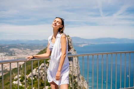 Gibraaltar. Tourist tiredly relaxed her shoulders and her hands hung lashes, closed her eyes and stands on a bridge over the ocean