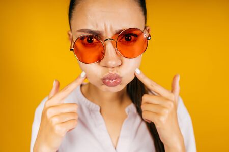 the girl puffed out her cheeks and presses them with her fingers, collecting her lips with a tube. Eyebrows frown. background yellow