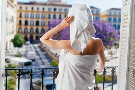 a hotel guest stands with her back to the camera on the balcony and looks at the European city. she after the shower with a towel on her head and wrapped in a sheet Banco de Imagens