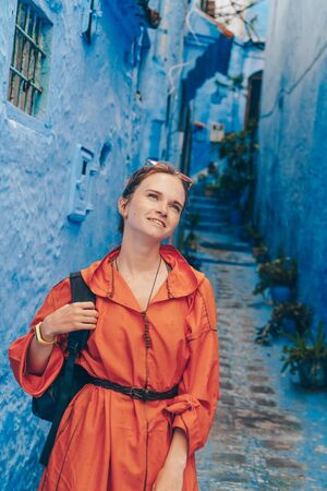girl with a cute smiling backpack looks up to the sky in the blue city of morocco Banco de Imagens