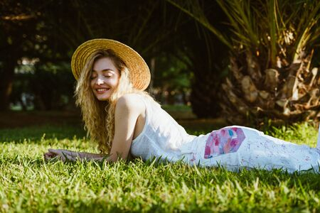 girl joyfully smiling closed her eyes, lies on the grass in the park Banco de Imagens