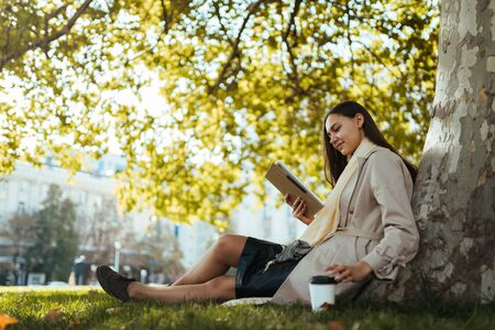 student sitting under a tree, drinking coffee and looking at a tablet pc Banco de Imagens