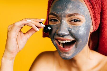 a girl with a coal mask on her face laughs joyfully. background yellow