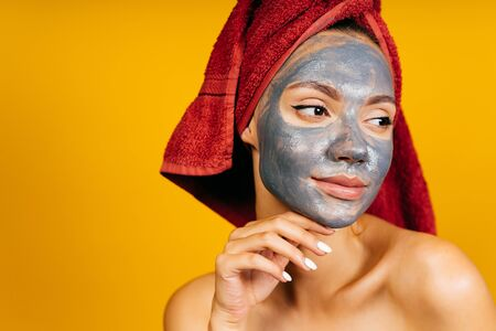 girl with a charcoal mask on her face thoughtfully touches her chin with her hand Banco de Imagens