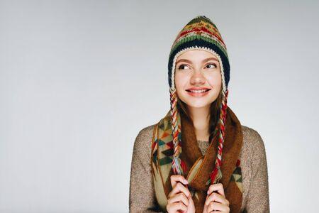 北の人々の冬の帽子をかぶった女の子がカメラでかわいい笑みを浮かべています。灰色の背景