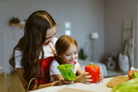 daughter sits in her mothers arms and they sort vegetables together in the kitchen Standard-Bild - 134850728