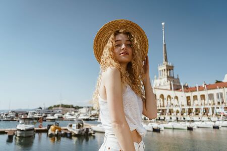 curly blonde looks down at the camera on the background of the sea and boats 版權商用圖片