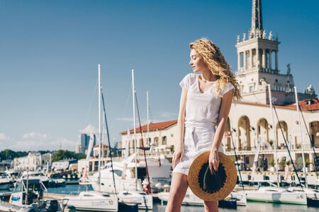 blonde beauty stands shrugging her shoulders against the backdrop of the seaport and boat boats