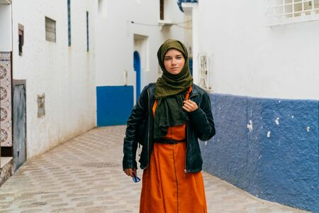 Muslim woman in a headscarf and a bright dress under a leather jacket, with a backpack on a street in Morocco
