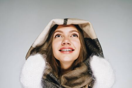 a girl in warm clothes, unusually romantic, raised her chin and smiles with radiant eyes with delight. gray background
