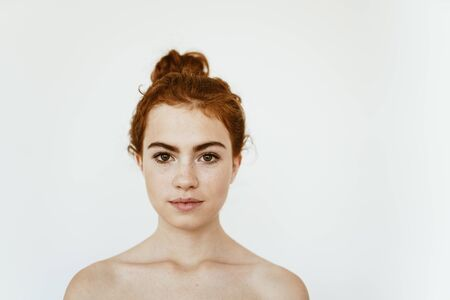 a girl with a beautiful face and natural make-up, hair is gathered in a bun on the top, shoulders are bare, background gray Stock Photo