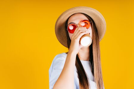 girl in a hat and sunglasses drinks coffee from a paper cup. yellow background