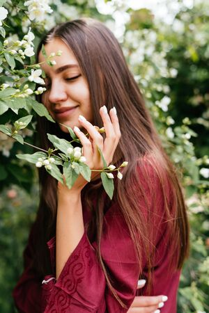 the beautiful nymph inhales the aroma of jasmine flowers with pleasure, covering her eyes with pleasure Stock Photo