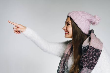 a girl in warm clothes stands in profile, stretching out her hand and pokes her index finger forward, smiling joyfully with satisfaction, as if she recognized someone. gray background
