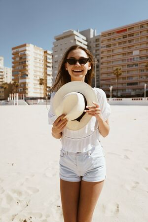 a tourist on the beach stands in summer clothes, covers her shoulders with a hat and smiles joyfully playfully, pointing a finger at the camera, wearing black glasses