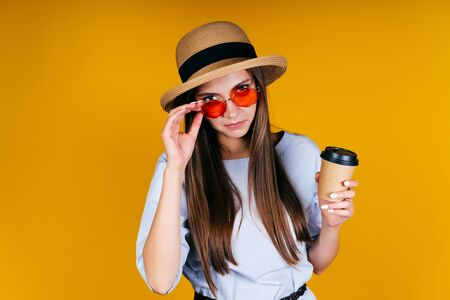 a girl in a hat, lowered her glasses with her hand and looks seriously at the camera with a question of serious aggression in her gaze (look says: What is needed?), coffee in hand, background yellow Stock Photo