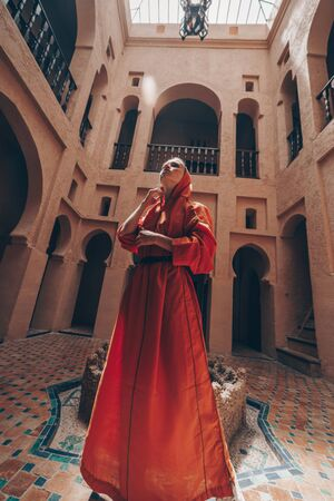 girl in the temple of morocco stands in the middle in a dress with a hood
