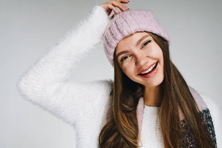 a girl in a knitted hat and a fluffy sweater smiles broadly and touches the top of her hand. gray background