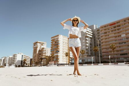 a girl in a hat and sun glasses stands with her legs crossed barefoot in the sand against the background of buildings Stock Photo