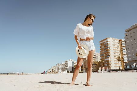 the girl on the beach is looking upset for something on the sand beneath her feet. behind the building