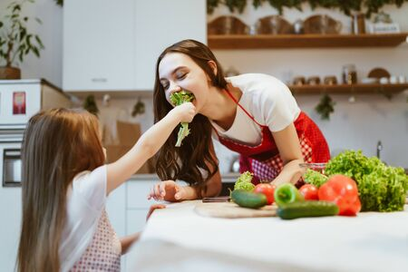 mom and daughter in the kitchen. daughter feeds mom with lettuce