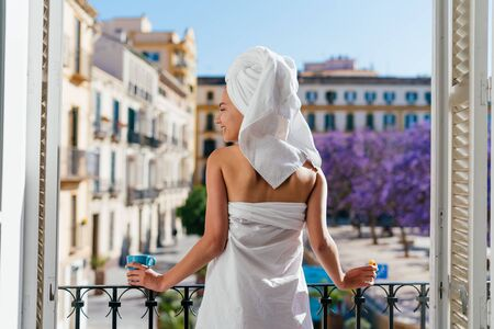 the hotel guest stands at the open window and looks out onto the street, a towel on her head, her body wrapped in a sheet, her back to the camera Stock Photo